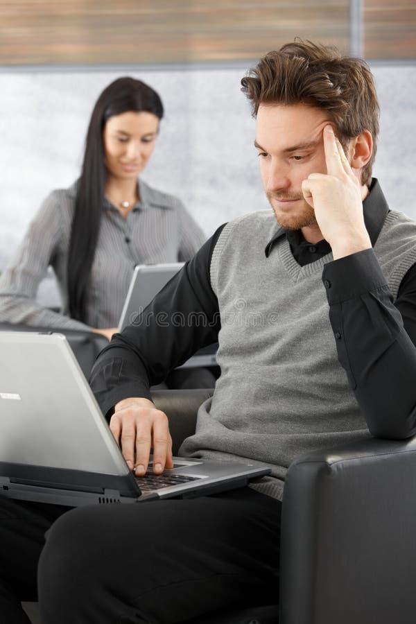 Молодой бизнесмен работая на компьтер-книжке стоковое фото rf