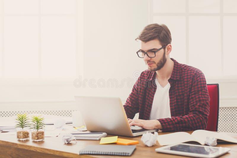 Молодой бизнесмен работая с компьтер-книжкой в современном белом офисе стоковая фотография