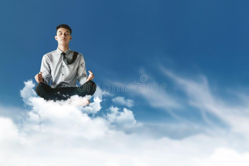 Молодой бизнесмен распологая на облако над небом с medita йоги стоковые фото