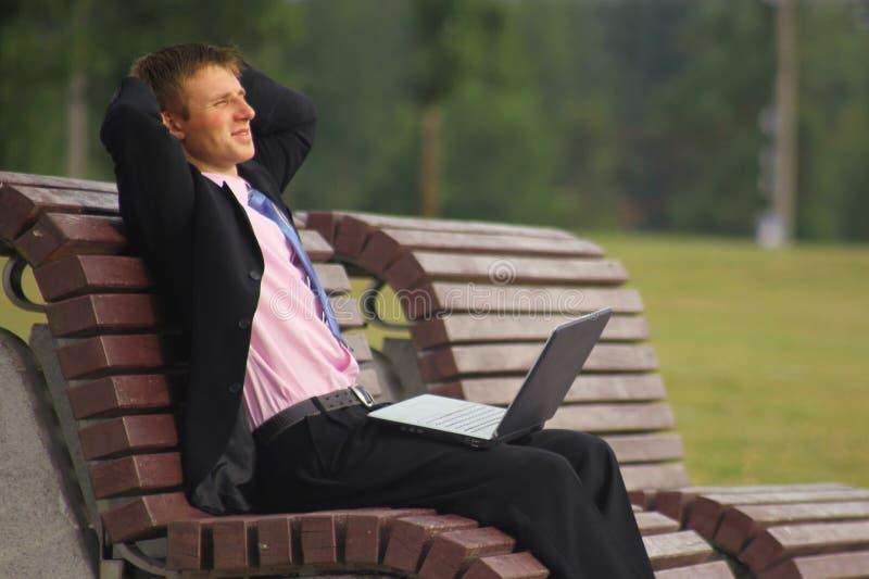 Молодой бизнесмен сидит на парке и использует компьтер-книжку стоковые фотографии rf