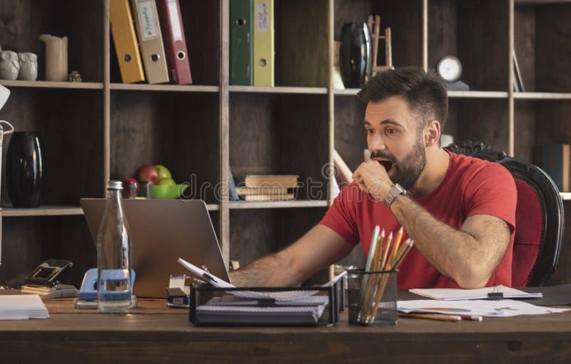 Молодой бизнесмен сидя в студии с компьтер-книжкой и удивительно изумительными новостями стоковые изображения
