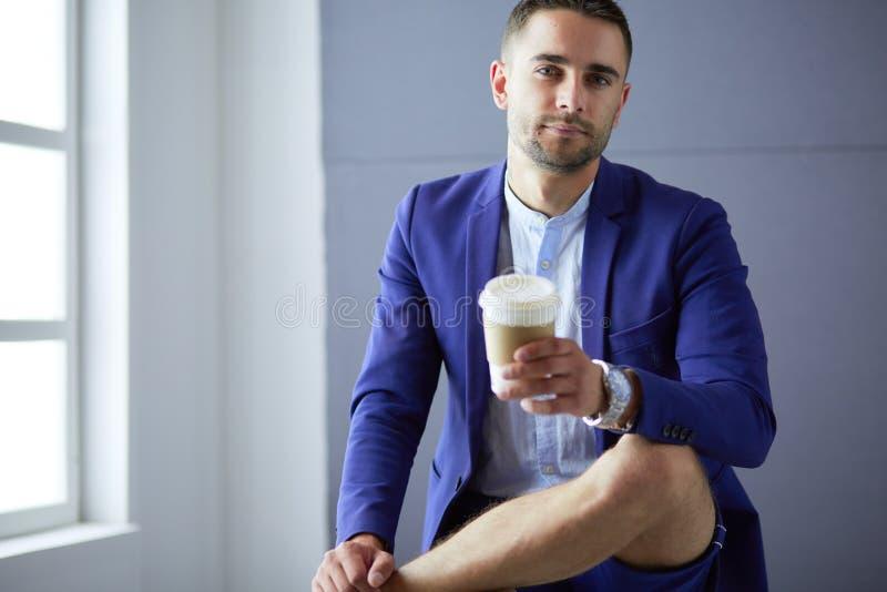 Молодой бизнесмен сидя на серой предпосылке стоковое изображение