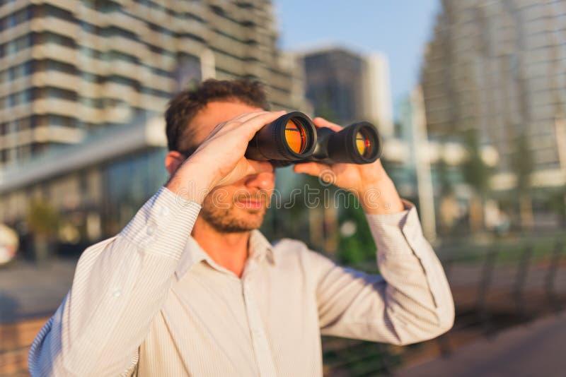 Молодой бизнесмен смотря через бинокли с офисными зданиями на заднем плане стоковое изображение rf