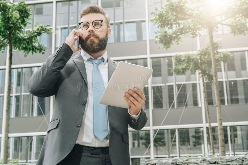 Молодой бизнесмен стоит внешним, держит планшет и говорит на его сотовом телефоне стоковое фото