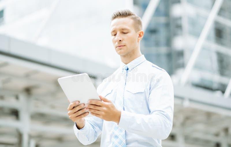 Молодой бизнесмен, стоящий рядом со зданием офиса и использующий цифровой планшетный компьютер Мобильные технологии и концепция с стоковое фото