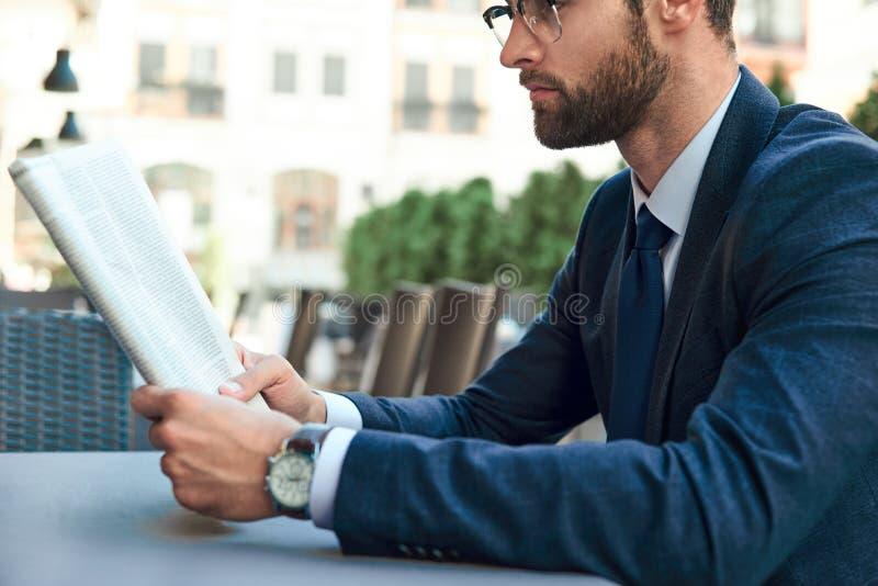 Молодой бизнесмен с бородой и нося стеклами читает газету стоковые изображения