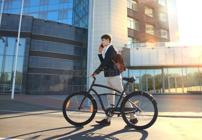 Молодой бизнесмен с велосипедом и smartphone на улице города стоковые фотографии rf