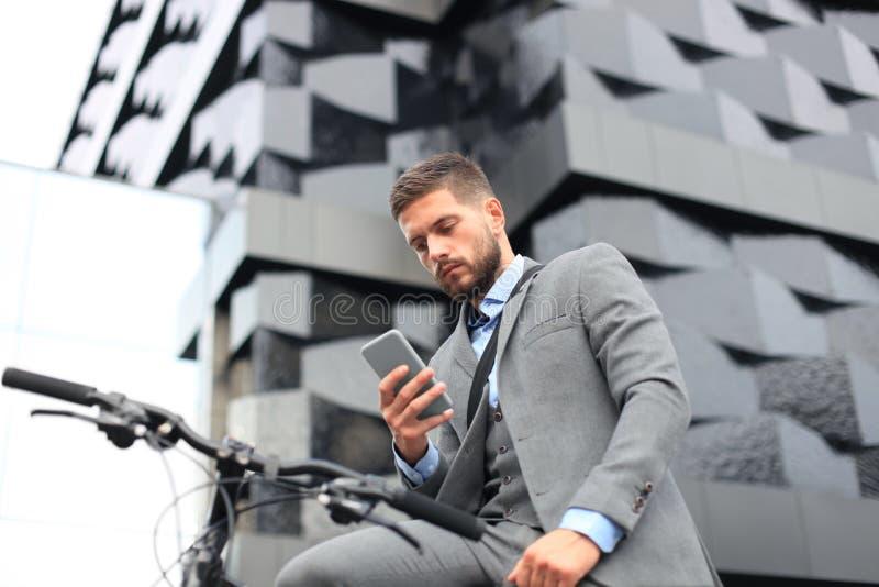 Молодой бизнесмен с велосипедом и smartphone на улице города стоковое фото rf