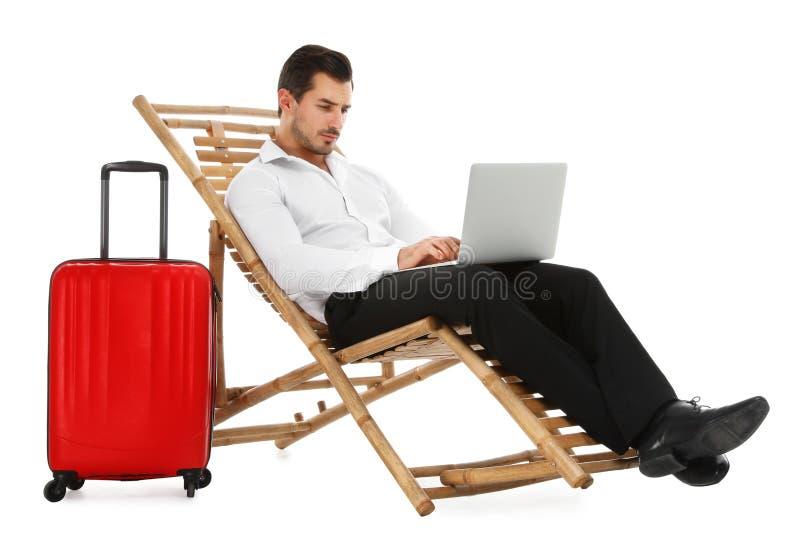 Молодой бизнесмен с ноутбуком и чемоданом на шезлонге против белизны Аксессуары пляжа стоковые изображения rf