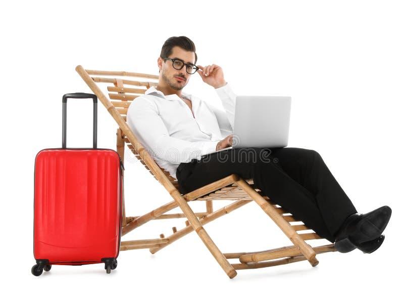 Молодой бизнесмен с ноутбуком и чемоданом на шезлонге против белой предпосылки стоковые изображения rf