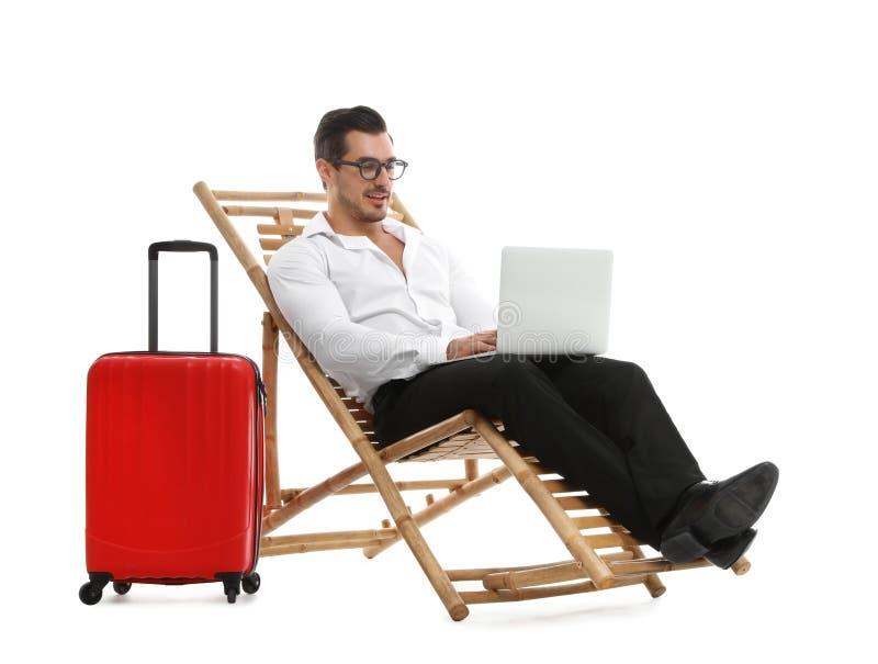 Молодой бизнесмен с ноутбуком и чемоданом на шезлонге против белой предпосылки стоковые фотографии rf