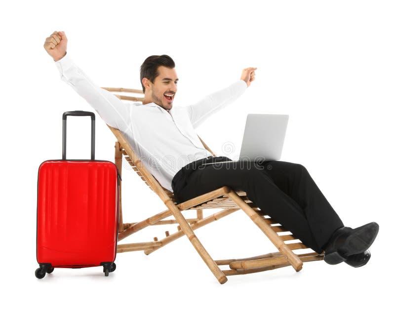 Молодой бизнесмен с ноутбуком и чемоданом на шезлонге против белой предпосылки E стоковая фотография