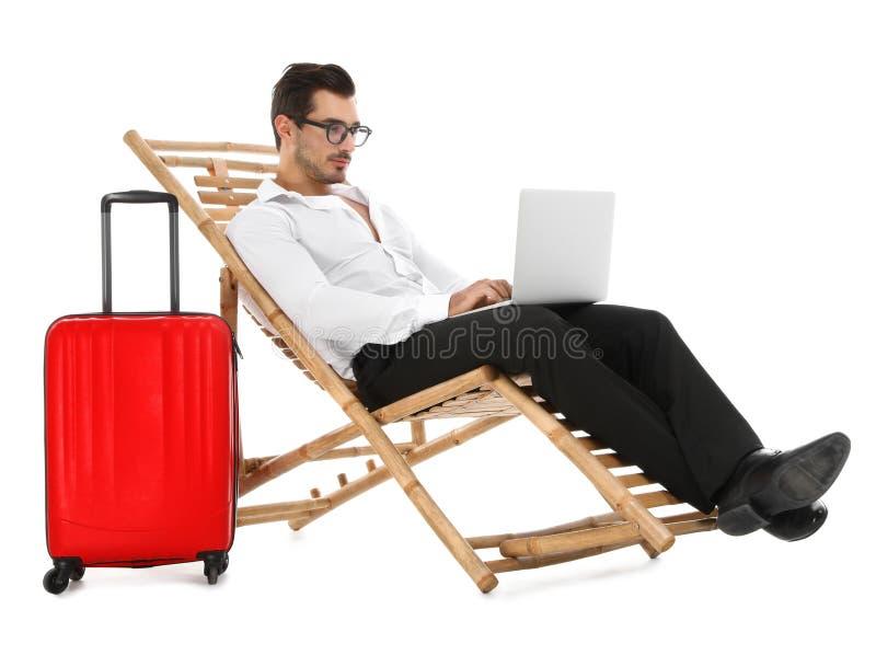 Молодой бизнесмен с ноутбуком и чемоданом на шезлонге против белой предпосылки стоковое фото