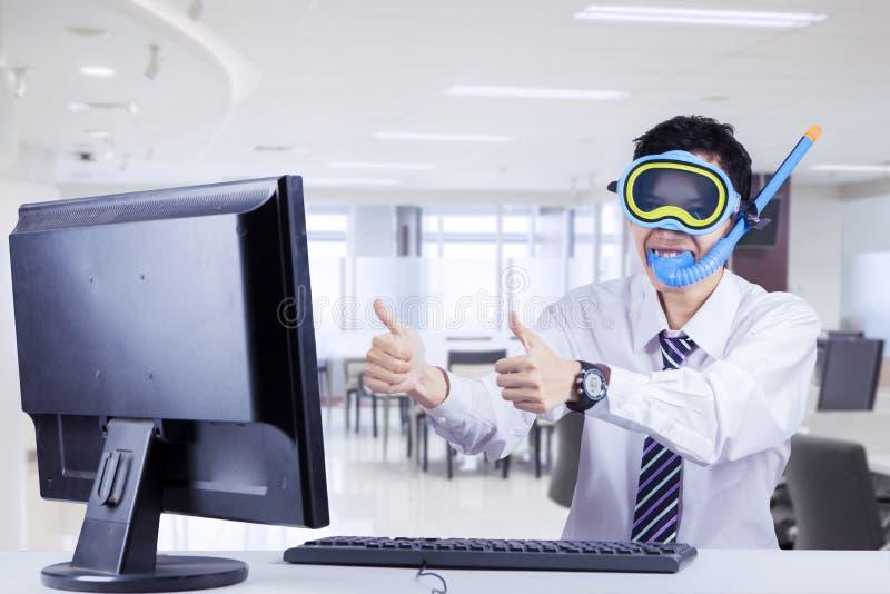 Молодой бизнесмен с снаряжением для подводного плавания в офисе стоковое изображение