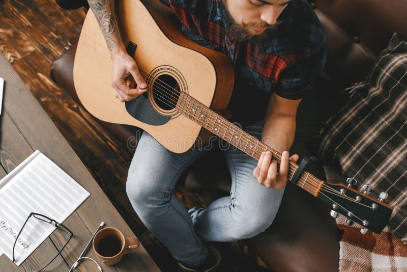 Молодой битник гитариста дома играя конец-вверх взгляд сверху гитары стоковое фото rf