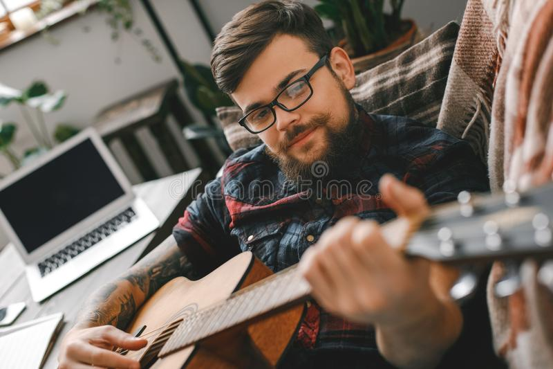Молодой битник гитариста дома при гитара лежа играющ конец-вверх стоковые фото