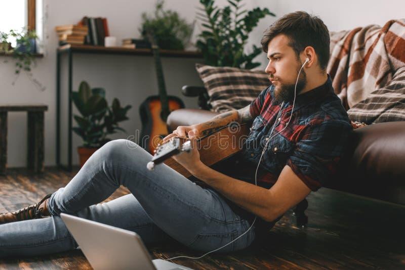 Молодой битник гитариста дома сидя на поле держа наушники гитары слушая звучит стоковые фото