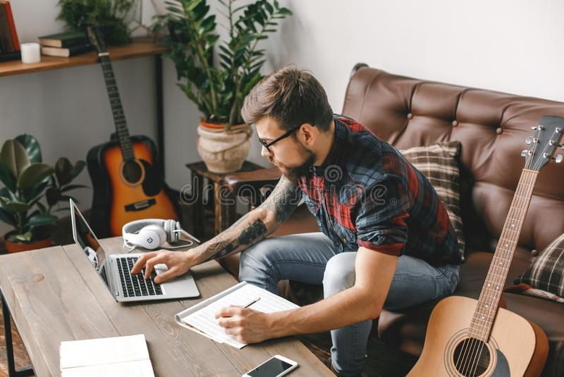 Молодой битник гитариста дома с сочинительством компьтер-книжки просматривать гитары стоковые изображения