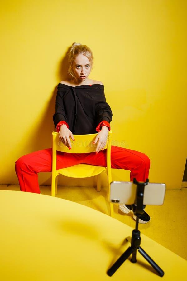 Молодой блоггер девушки моды одетый в красных брюках и черной куртке принимает selfie на положении смартфона possing стоковые изображения rf