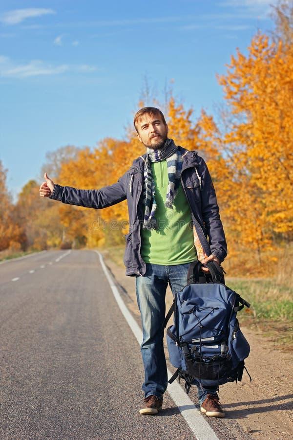 Молодой бородатый автостопщик хипстера с попыткой рюкзака к автомобилю задвижки стоковые изображения