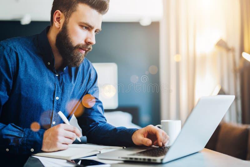Молодой бородатый бизнесмен работает на компьютере, принимает примечания в тетради, анализирует информацию, делает бизнес-план стоковое изображение