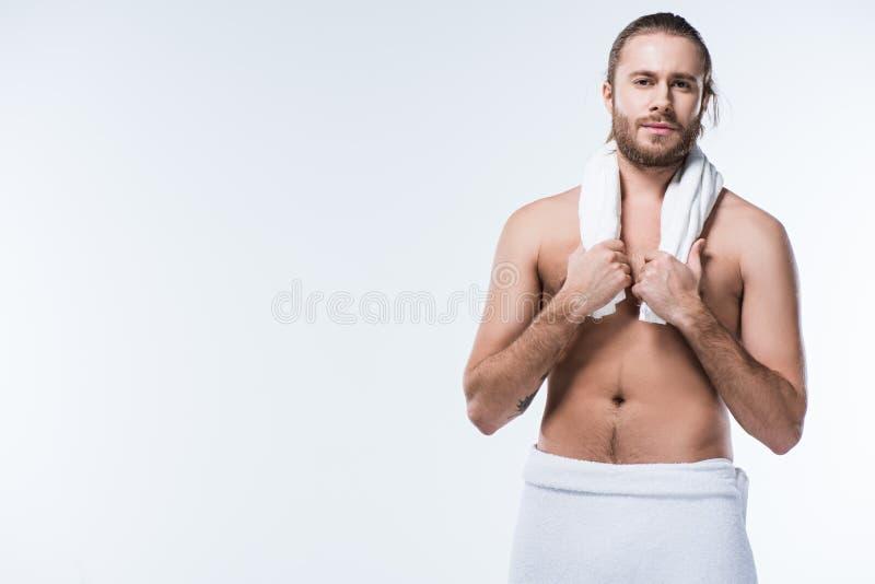 Молодой бородатый кавказский человек держа полотенце ванны вокруг его шеи и смотря камеру, стоковые изображения