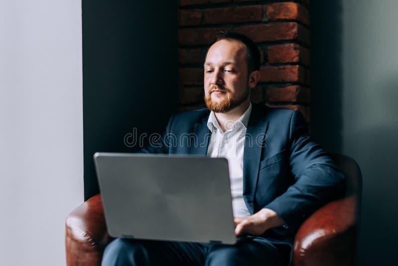 Молодой бородатый мужской бизнесмен сидит и работает в ноутбуке в современном интерьере стоковая фотография