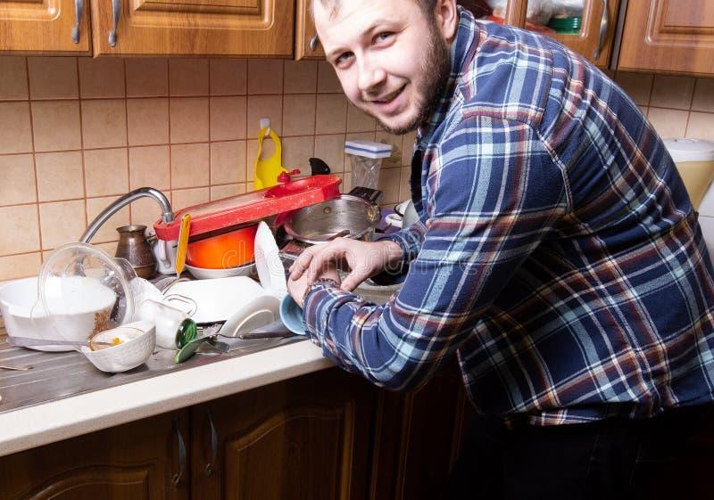 Молодой бородатый парень смотрит его дозор и счастливым количеством грязных блюд лежа в кухонной раковине Он имеет время помыть стоковые фотографии rf