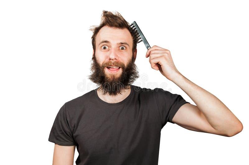 Молодой бородатый перерастанный гребень удерживания человека и расчесывать его волосы r стоковая фотография