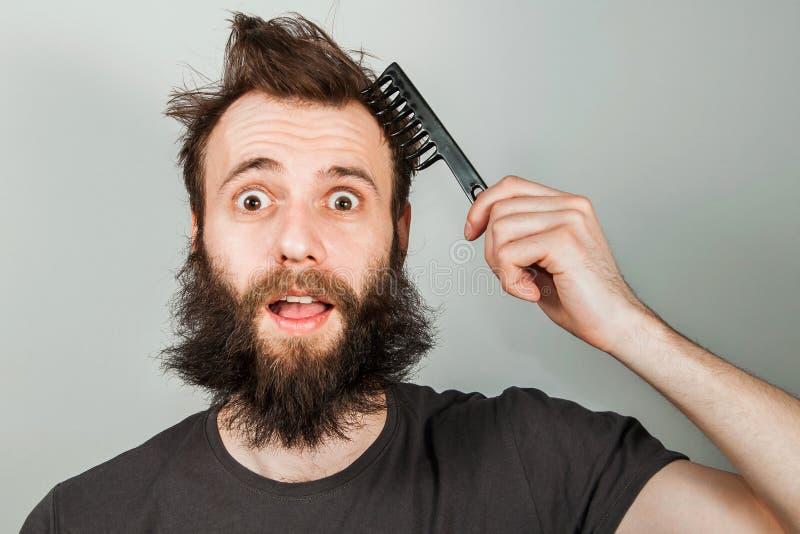 Молодой бородатый перерастанный гребень удерживания человека и расчесывать его волосы Близкий поднимающий вверх портрет на серой  стоковое изображение rf