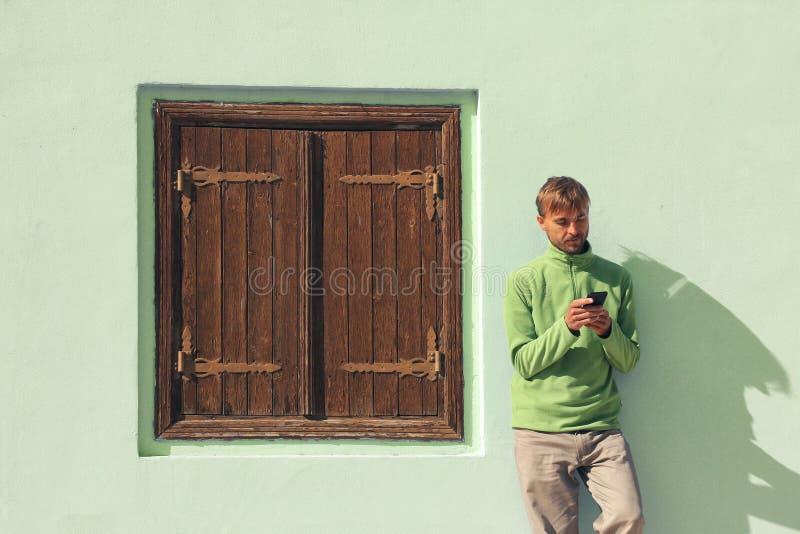 Молодой бородатый человек в зеленых стойках рубашки около стены со старым деревянным смартфоном окна и польз Концепция минимализм стоковое изображение