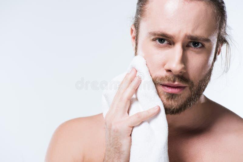 Молодой бородатый человек смотря к камере пока держащ полотенце ванны в руке близко к его щеке, стоковое фото