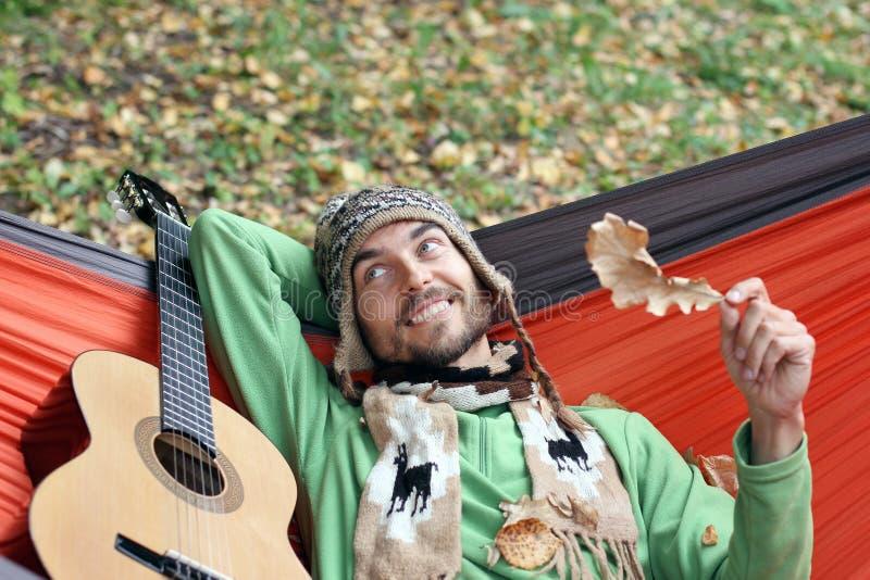 Молодой бородатый человек с гитарой ослабляет в гамаке в осени f стоковое изображение