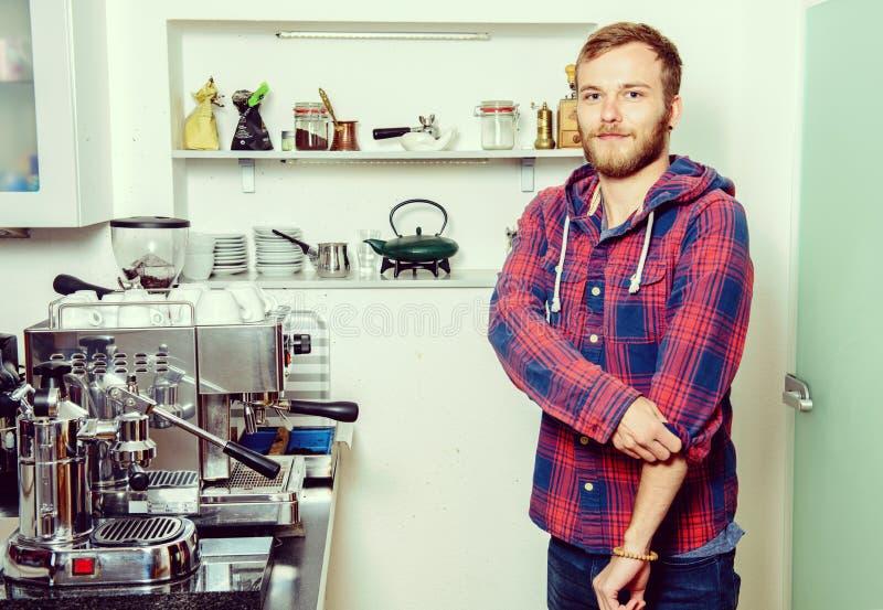 Молодой бородатый человек с его машиной эспрессо стоковые фотографии rf