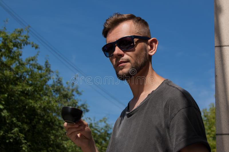 Молодой бородатый человек с чашкой кофе в его руке против голубого неба на солнечный летний день стоковые изображения rf