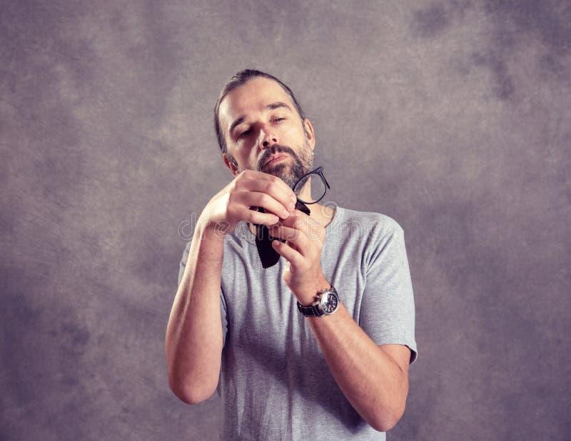 Молодой бородатый человек ceaning его стекла стоковые изображения