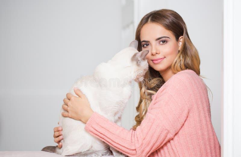 Молодой брюнет с ее котом стоковые фото