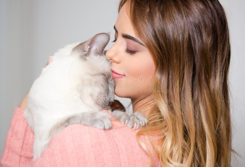 Молодой брюнет с ее котом стоковая фотография