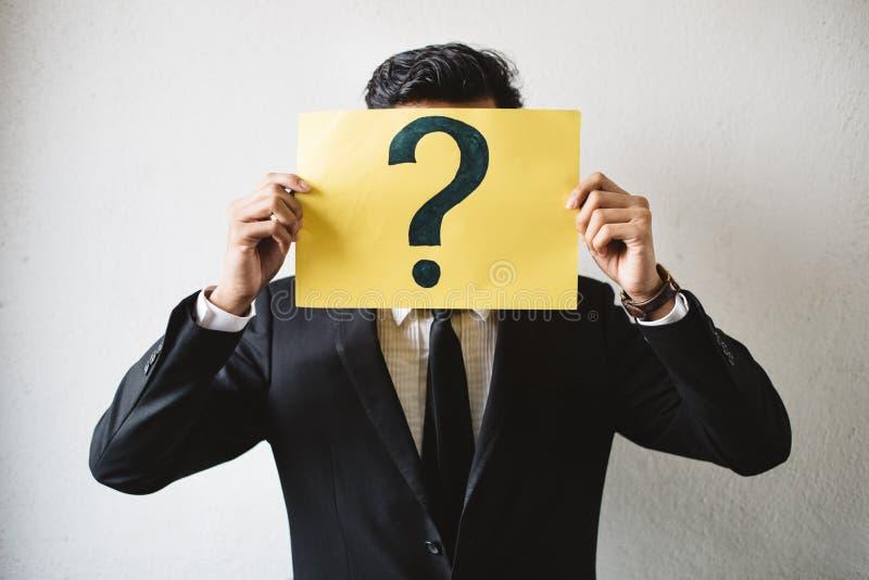 Молодой взрослый азиатский бизнесмен держа желтую бумагу шильдика с ВОПРОСИТЕЛЬНЫЙ ЗНАК стоковые фотографии rf