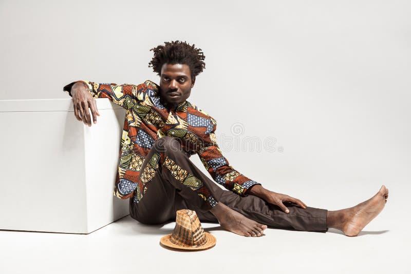 Молодой взрослый африканский человек, сидя на поле около coub стоковая фотография