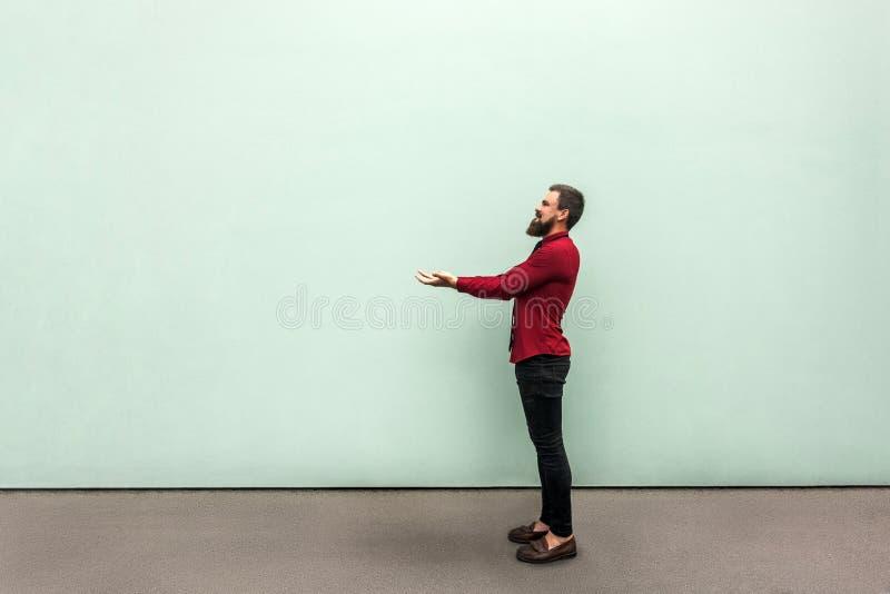 Молодой взрослый бородатый человек держа что-то тяжелый и показывая его стоковое изображение rf