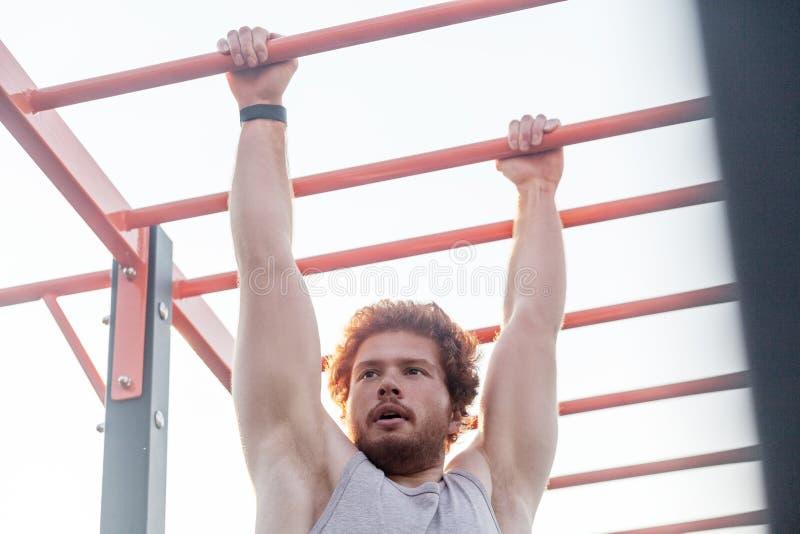 Молодой взрослый бородатый человек redhead, подъем на баре стоковое фото