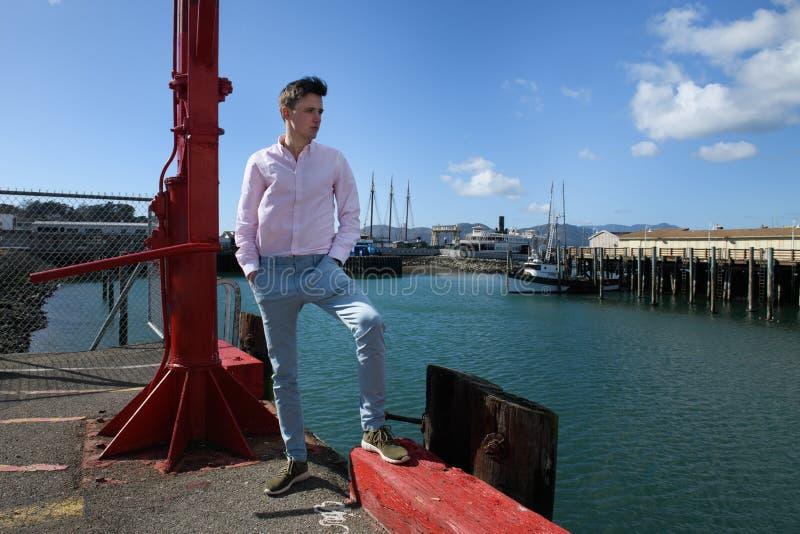 Молодой взрослый модный человек нося голубые брюки и классическую футболку стоя на груше города думать стоковая фотография