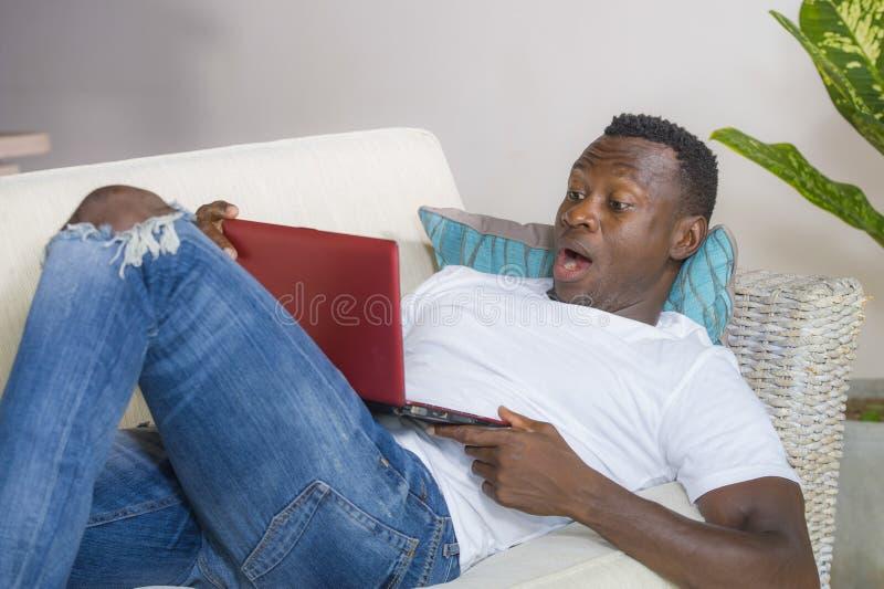 Молодой возбужденный и удивленный молодой черный Афро-американский человек в сети выражения стороны неверия и удара с ноутбуком стоковые фотографии rf