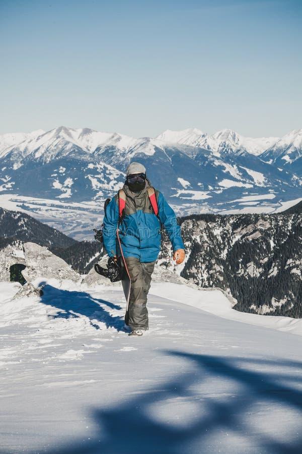 Молодой восторженный snowboarder идя вверху гора с сноубордом в его руке стоковая фотография