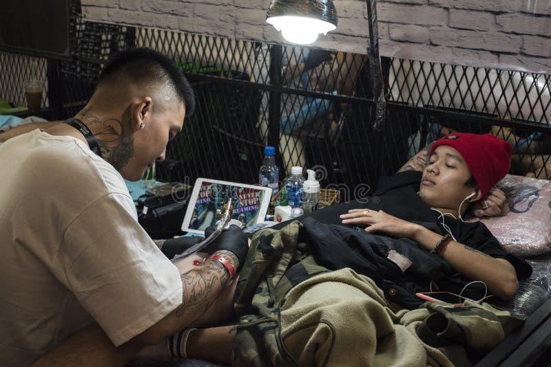 Молодой въетнамский человек лежа вниз носящ красную шерстяную шляпу получает татуировку на его верхней правой бедренной кости сту стоковое фото rf