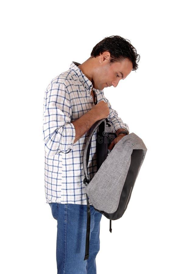 Молодой высокорослый человек смотря в его рюкзак стоковая фотография rf