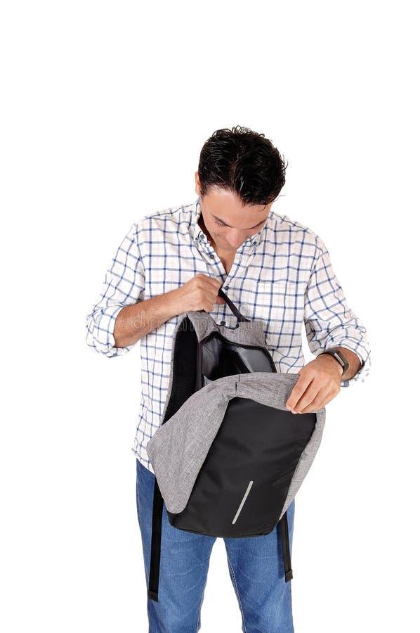 Молодой высокорослый человек смотря в его рюкзак стоковое фото rf