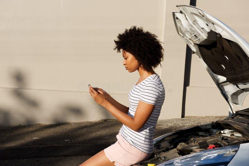 Молодой готовить чернокожей женщины сломанный вниз с автомобиля и использование сотового телефона для помощи стоковые фото