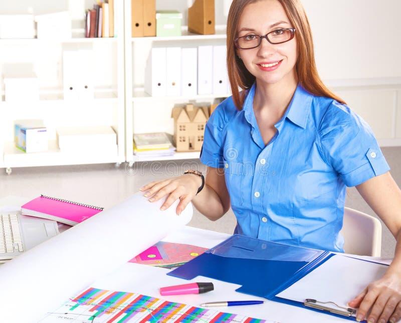 Молодой график-дизайнер работая на компьтер-книжке используя таблетку дома стоковые фото